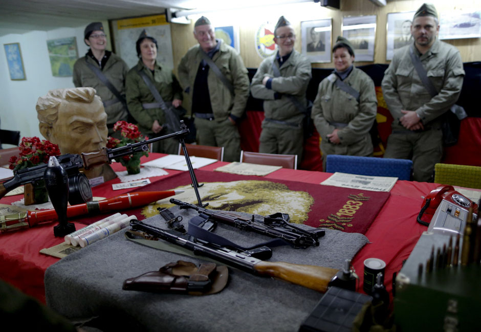 Participants dressed as NVA soldiers look at weapons during the 'reality event' one night at the 'Bunker-Museum' in Rennsteighoehe