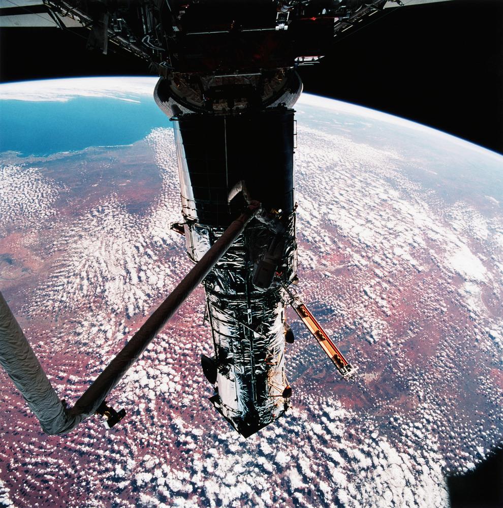 """Αστροναύτης κρεμασμένος ανάποδα (πλάκα κάνουμε, δεν υπάρχει """"ανάποδα"""" στο διάστημα) επισκευάζει το τηλεσκόπιο. Στο φόντο, τούτη η Γης που την πατούμε"""