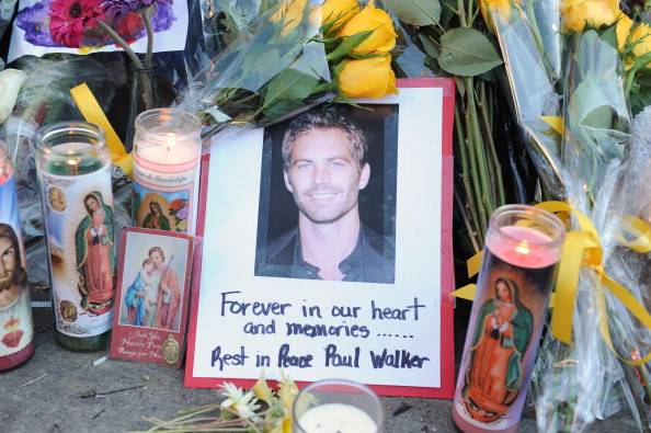 "A photo of actor Paul Walker is seen December 1, 2013 among flowers and candles left by fans at the site of the car accident in which the ""Fast and Furious"" actor and another man died the previous day, in Santa Clarita, California. Santa Clarita police warned fans Monday against ""burning rubber"" near the spot where the car Walker was a passenger in crashed, as they continued to probe the accident. Police issued the caution after reports of people pulling stunt maneuvers on the stretch of road in town northwest of Los Angeles, where Walker died on Saturday. AFP PHOTO / Robyn Beck (Photo credit should read ROBYN BECK/AFP/Getty Images)"
