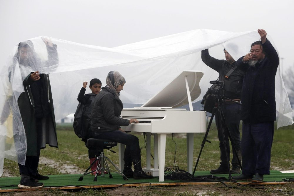 epa05208051 Chinese contemporary artist, Ai Weiwei (R) protects himself and others from the rain, as Nour Al Khizam (C) from the city Deirez Zor, Syria, plays the piano during a performing at a refugee camp, at the border of Greece and the Former Yugoslav Republic of Macedonia (FYROM), near Idomeni, Northern Greece, 12 March 2016. Greece has some 36,000 migrants trapped due to entry restrictions imposed by Macedonia in recent months. EPA/YANNIS KOLESIDIS