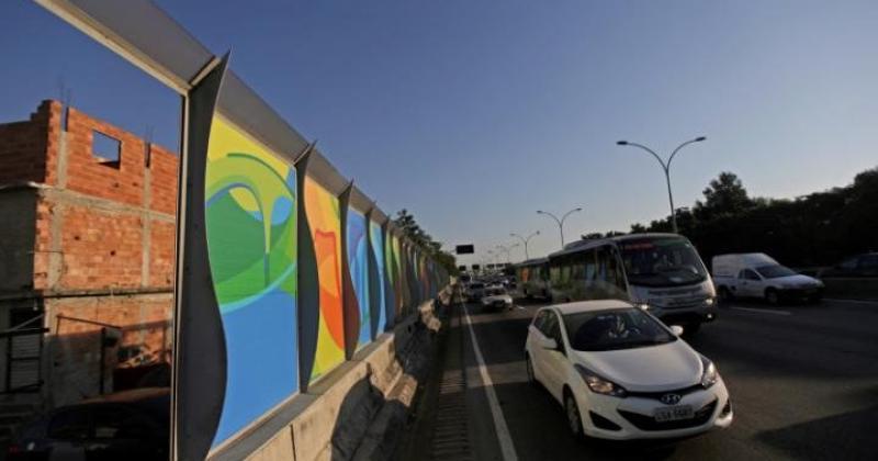 """Πολύχρωμος """"Ολυμπιακός"""" φράχτης κατά μήκος του δρόμου από το αεροδρόμιο προς τα γήπεδα, για να μη μολύνεται το βλέμμα των επισκεπτών από τις φαβέλες"""