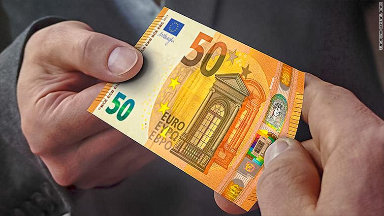 Δύο άντρες τσακώνονται για το ποιος θα πάρει το νέο χαρτονόμισμα των 50 ευρώ με χρώμα πάπρικας